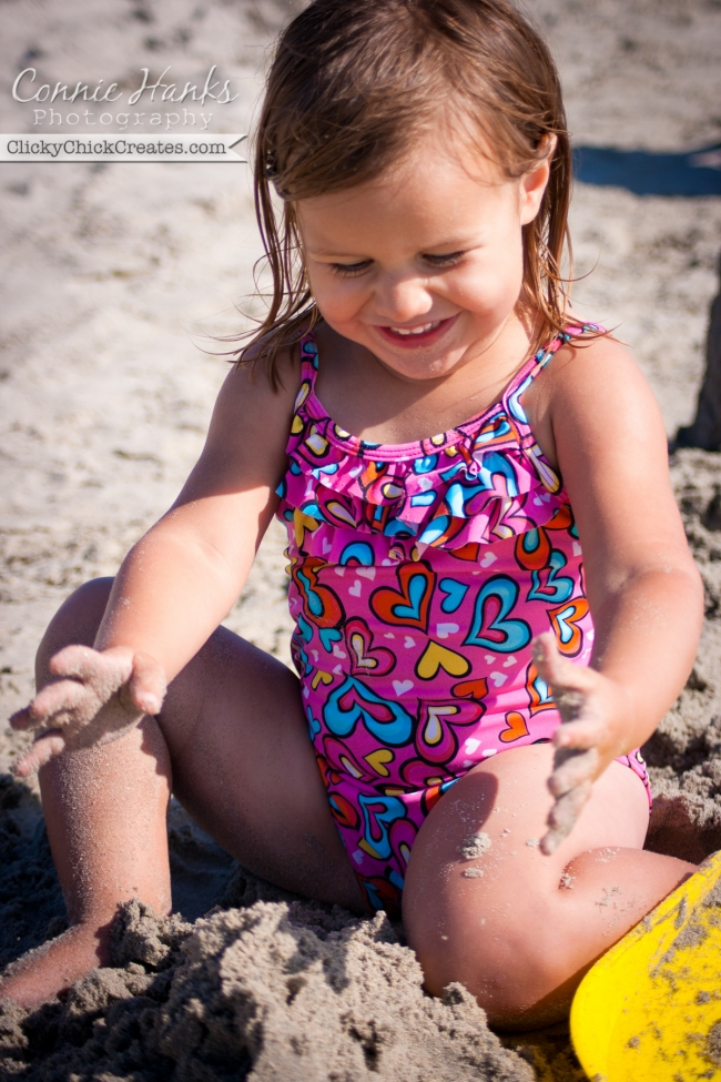 Connie Hanks Photography  //  ClickyChickCreates.com  //  baby girl enjoying building sand castles at beach on sunny day