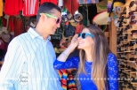 Connie Hanks Photography // ClickyChickCreates.com // engagement couple session, Rosarito, Mexico, mercado, market, colorful, turquoise, blue, gray, wood, wheel, rustic, arches, archways, kiss, sunglasses, hipsters