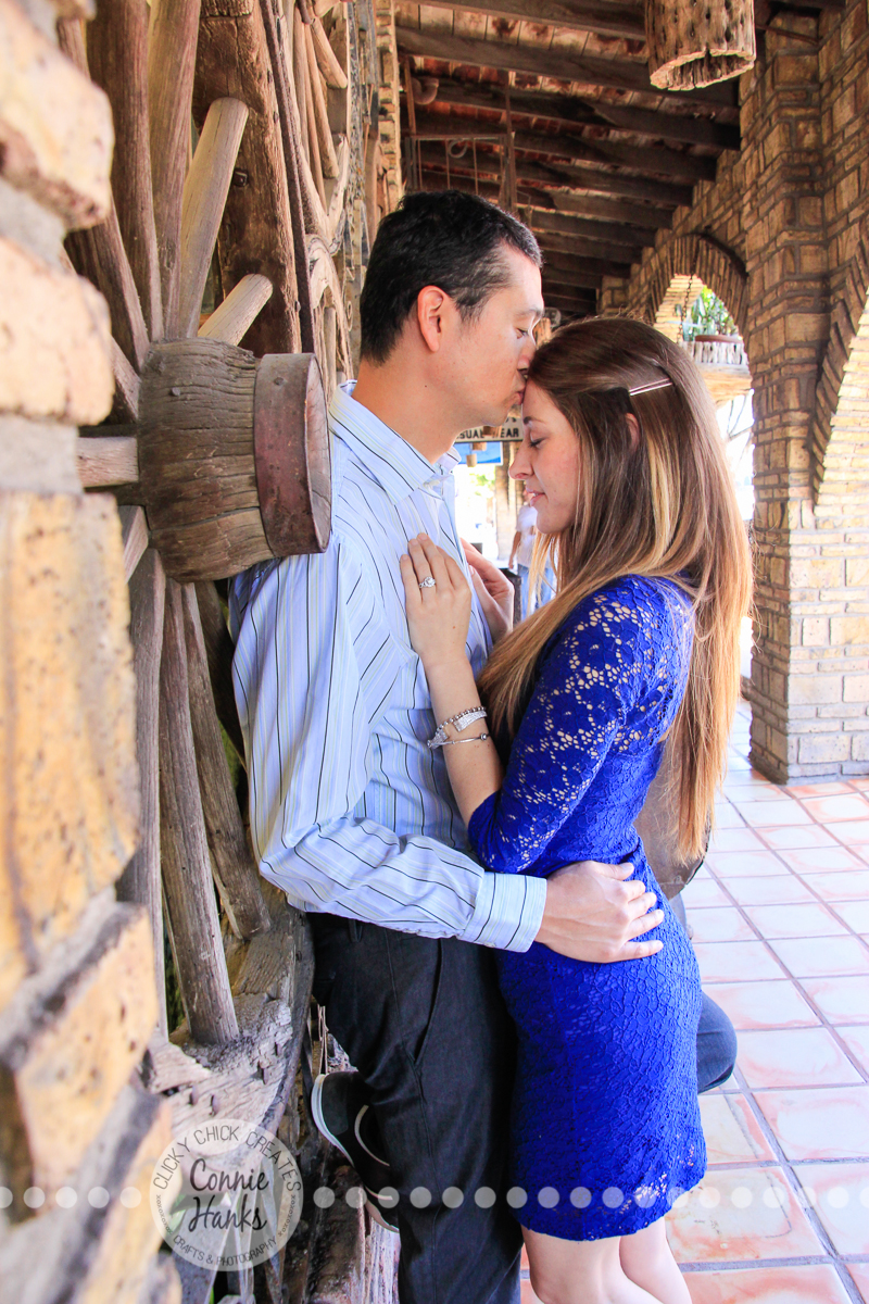 Connie Hanks Photography // ClickyChickCreates.com // engagement couple session, Rosarito, Mexico, mercado, market, colorful, blue, gray, wood, wheel, rustic, arches, archways, kiss