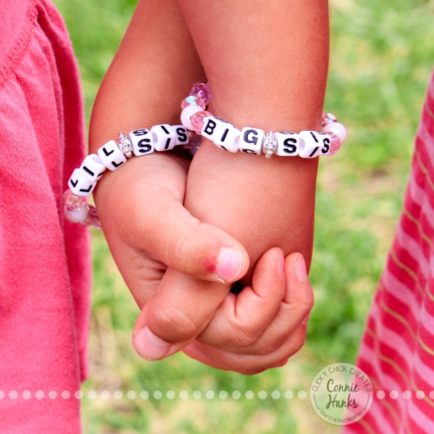 "Connie Hanks Photography // ClickyChickCreates.com // Handful of Sisterly Love, little girls wearing matching ""Big Sis"" and ""Lil Sis"" bracelets"
