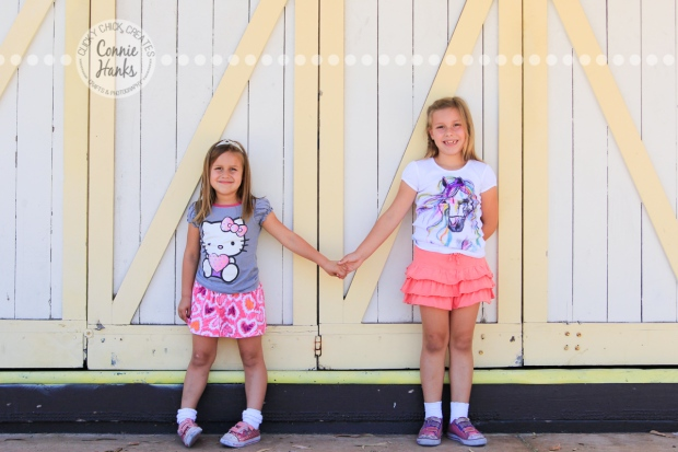 Connie Hanks Photography // ClickyChickCreates.com // Sisters holding hands, photos in front of yellow and cream barn doors
