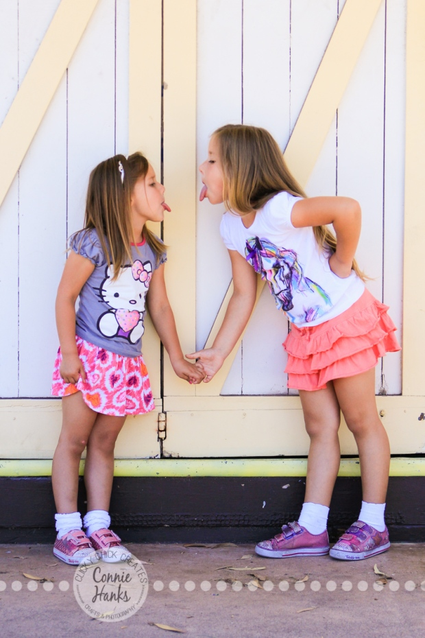 Connie Hanks Photography // ClickyChickCreates.com // Sisters holding hands, sticking tongues out, photos in front of yellow and cream barn doors